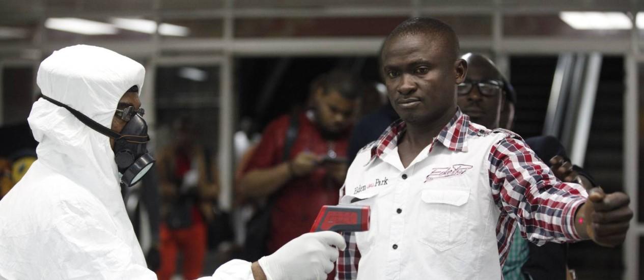Funcionário do Aeroporto Internacional de Lagos, na Nigéria, examina passageiro: país registrou casos de ebola no ano passado, mas autoridades acreditam que agora lidam com outra doença Foto: Sunday Alamba/AP