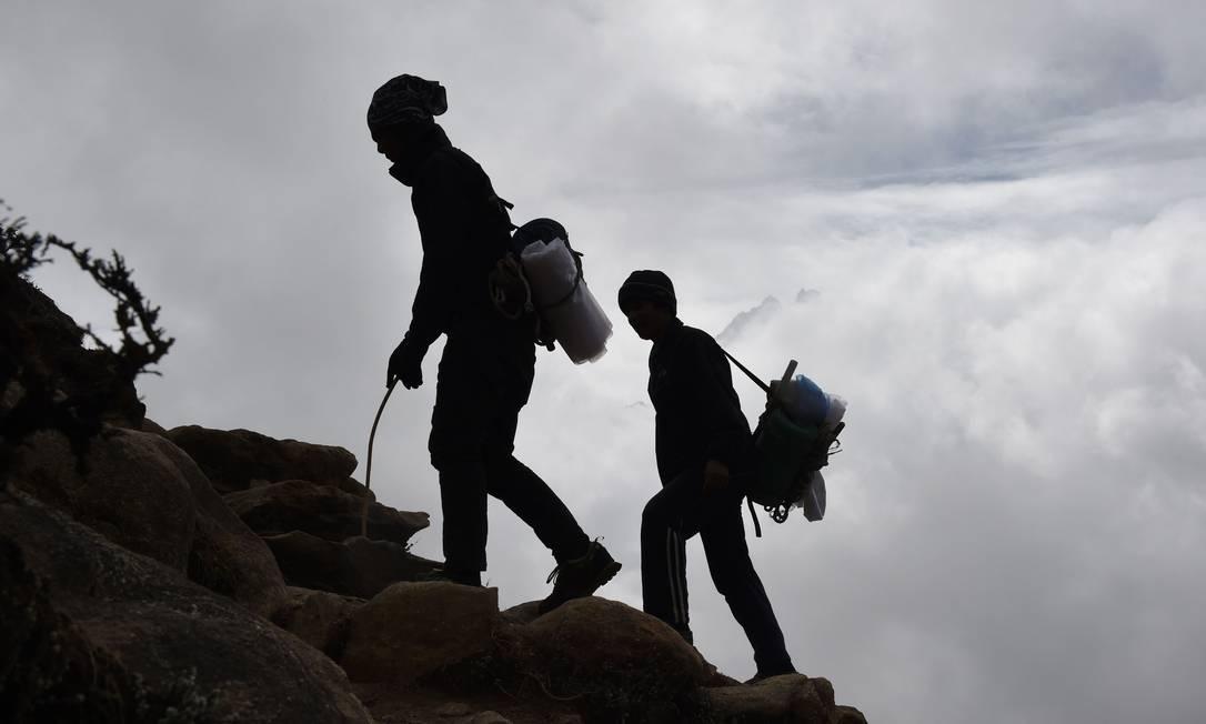 Carregadores nepaleses, que ganham entre US$ 40 e 60 por mês, e caminham em altitudes acima de 5 mil metros ROBERTO SCHMIDT / AFP