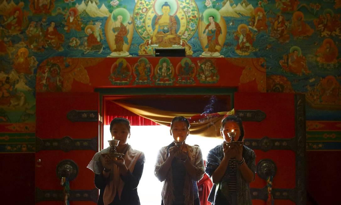 Filhas de Aan Kaji Sherpa, um dos 16 sherpas mortos na avalanche do ano passado, fazem homenagem ao pai no monastério de Kathmandu. Os guias estavam fixando cordas e transportando suprimentos para seus clientes estrangeiros que subiriam o pico de 8.850 metros NAVESH CHITRAKAR / REUTERS