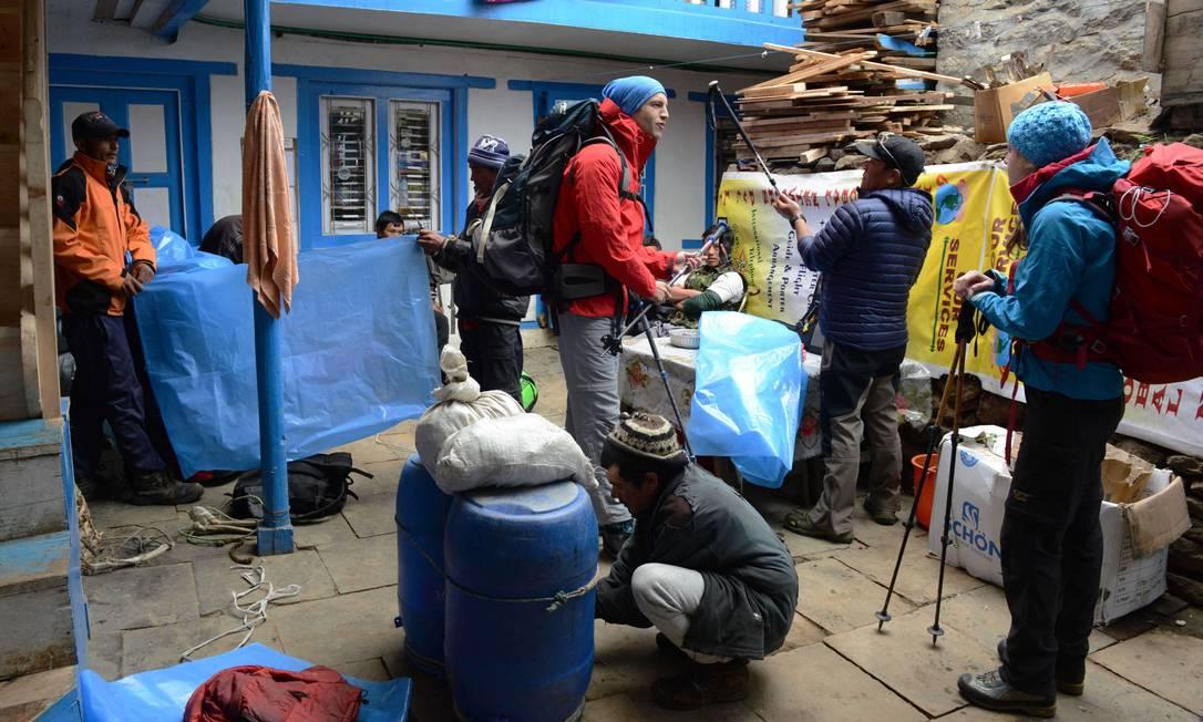 """O alpinista Sam Chappatte e sua namorada Alexandra Schneider aguardam os carregadores organizarem as bolsas que serão levadas à base do Everest. Na cidade himalaia de Lukla, emoção e medo. """"Foi simplesmente terrível ver tantos mortos"""", disse Chappatte, que voltou após o acidente de 2014 ROBERTO SCHMIDT / AFP"""