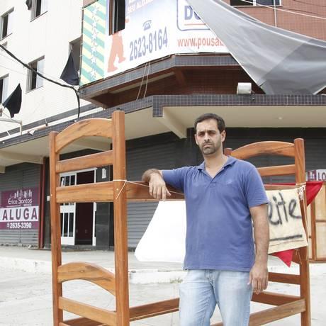Marcos, vendendo na rua os móveis da pousada que fechou Foto: Marcelo Carnaval/31-3-2015