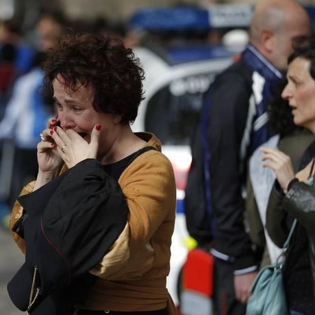 Uma mulher conversa no telefone em frente a colégico em Barcelona atacado por estudante de 13 anos Foto: Emilio Morenatti / AP