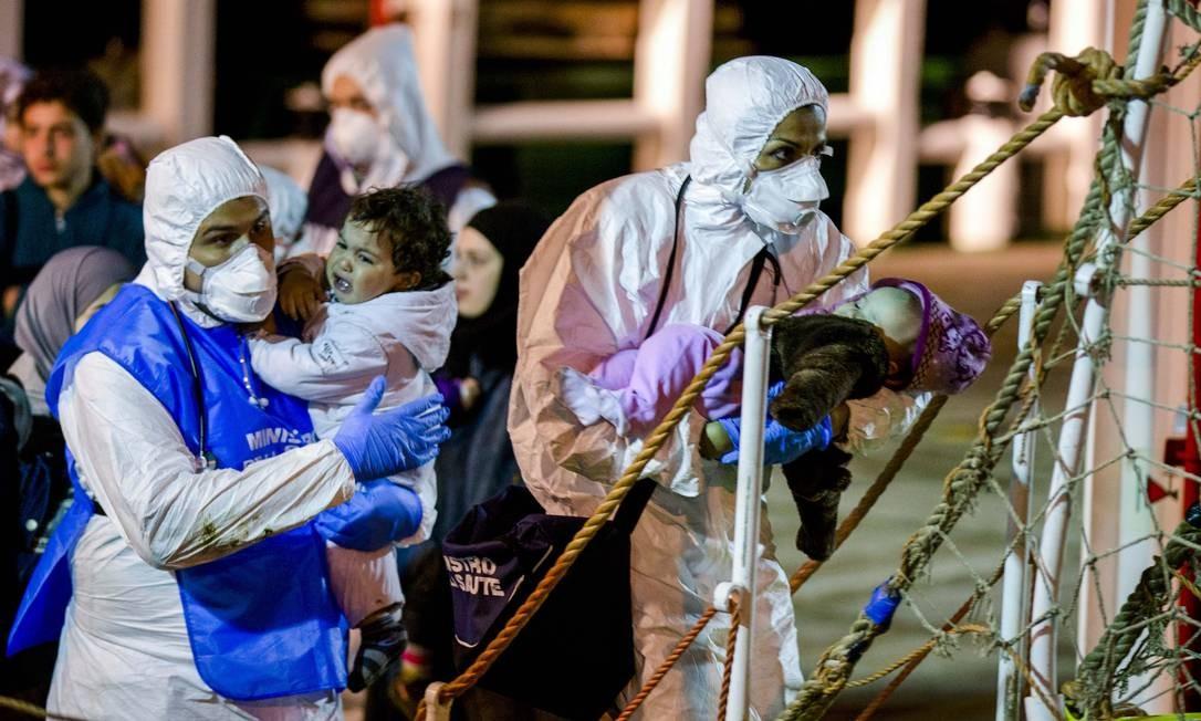 Resgatistas italianos ajudam a uma criança a desembarcar no porto de Pozzallo, na Sicília: cem imigrantes resgatados no domingo por um navio mercante Foto: Alessandra Tarantino / AP