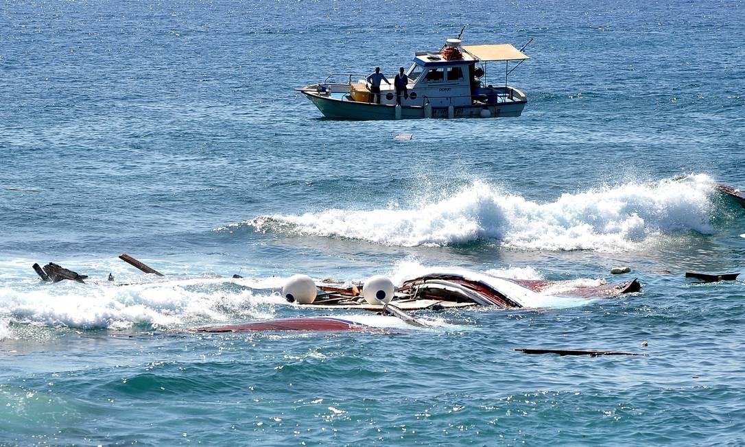 Barco pesqueiro passa por destroços de embarcação naufragada em Rhodes Foto: Nikolas Nanev / AP