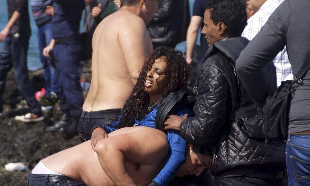Mulher é resgatada por um homem de um barco que naufragou perto de Rhodes Foto: EUROKINISSI / REUTERS
