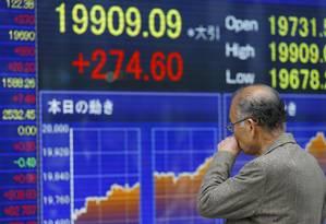 Um homem observa o painel eletrônico na Bolsa de Tóquio. O Índice Nikkei subiu 274,60 pontos, fechando a 19.909 pontos (1,40%) Foto: Shizuo Kambayashi / AP