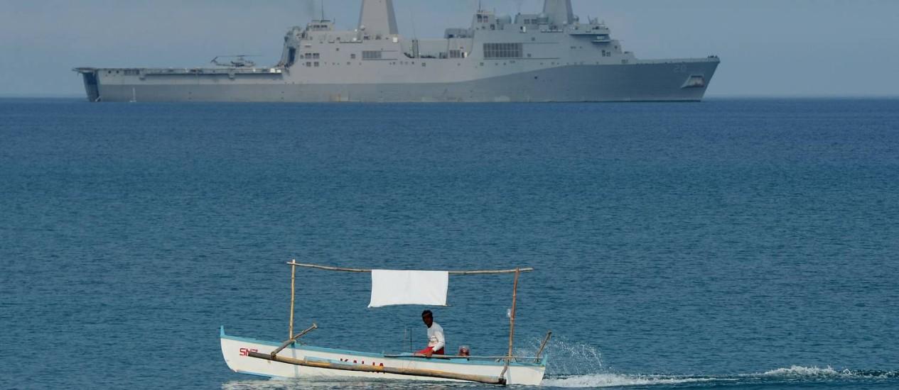 Pescador filipino passa por navio americano durante exercícios militares próximos ao recife de Scarborough, disputado por China e Filipinas Foto: TED ALJIBE / AFP
