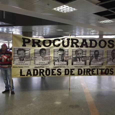 Sindicalistas exibem cartaz com fotos de deputados que aprovaram o texto-base do projeto de lei 4330 no Aeroporto de Vitória Foto: FUP/ Divulgação