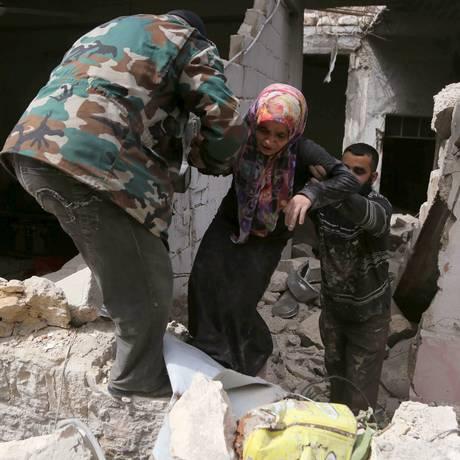 Moradores ajudam uma mulher a deixar escombros de sua casa após ataque aéreo realizado por forças leais ao presidente sírio, Bashar al-Assad, em al-Sakhour, um bairro de Aleppo Foto: HOSAM KATAN / REUTERS
