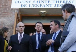 Primeiro-ministro francês, Manuel Valls (centro), o ministro do Interior da França, Bernard Cazeneuve (esq.), e o prefeito de Villejuif, Franck Le Bohellec, deixam a igreja Sainte Thérèse de l'Enfant Jesus em Villejuif, que supostamente seria alvo de ataque Foto: KENZO TRIBOUILLARD / AFP