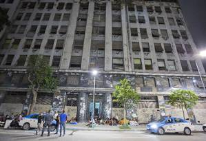 Invasores ficaram sentados na calçada, após serem retirados de prédio abandonado, no Centro Foto: Fernando Quevedo / Agência O Globo