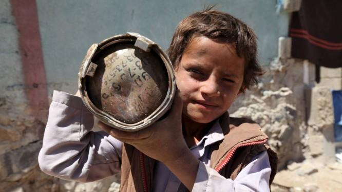 Menino iemenita mostra parte de um morteiro que encontrou após bombardeio da coalizão a Sanaa Foto: MOHAMED AL-SAYAGHI / REUTERS