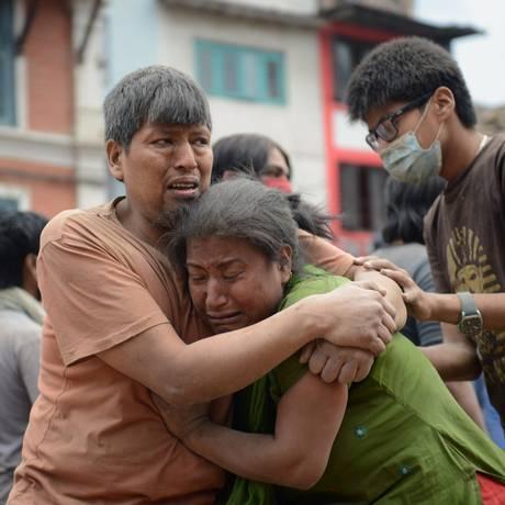 Casal nepalês se abarça na Praça Durbar em Katmandu. Terremoto matou mais de mil pessoas na manhã deste sábado Foto: PRAKASH MATHEMA / AFP