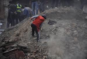 Pessoas limpam as ruas depois da Praça Durbar, Patrimônio Mundial da Unesco, ser arrasada pelo terremoto Foto: PRAKASH MATHEMA / AFP