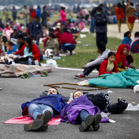 Muitos turistas dormiram em espaços abertos, junto com os moradores locais, que ficaram com medo de voltar para casa após os terremotos que atingiram a capital do Nepal Foto: Pratap Thapa / AP