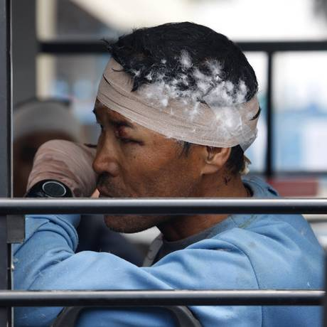 Guia xerpa machucado reflete sentado dentro de um ônibus depois do acampamento em que estava ser evacuado no Everest Foto: Bikram Rai / AP