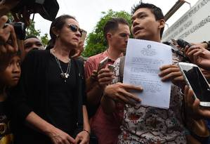 Angelita Muxfeldt (de preto), prima do brasileiro Rodrigo Gularte, ao lado do advogado indonésio Ricky Gunawan, que segura um laudo médico, fala a jornalistas após sair da prisão de Nusakambangan Foto: ROMEO GACAD / AFP