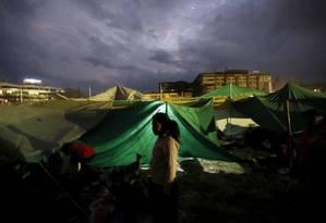 Uma criança em frente à tenda construída às pressas para passar à noite Foto: ADNAN ABIDI / REUTERS