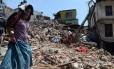 Uma mulher nepalesa passa por uma casa danificada em Katmandu
