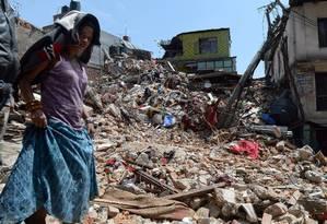Uma mulher nepalesa passa por uma casa danificada em Katmandu Foto: PRAKASH SINGH / AFP