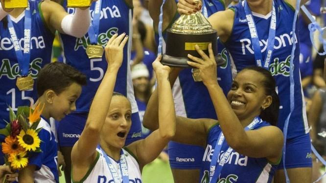 Pura Emoção. Fofão ergue a pesada taça de campeã da Superliga Feminina com a ajuda de Fabi (de branco) e Gabi Foto: Guito Moreto / Guito Moreto
