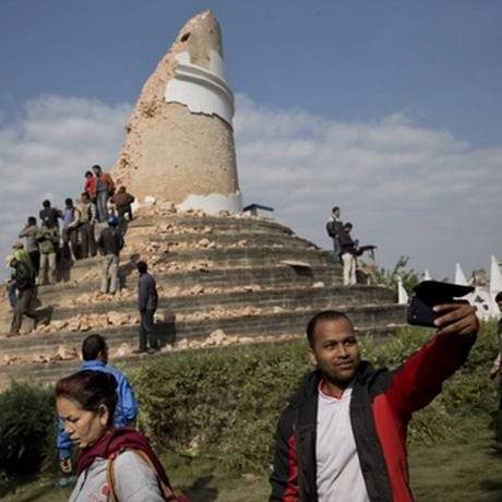 Homem tira selfie na torre de Torre Dharahara, marco histórico em Katmandu Foto: Bernat Armangue/AP