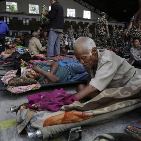 Vítimas do terremoto no Nepal aguardam ambulâncias no chão do aeroporto de Katmandu Foto: Altaf Qadri / AP