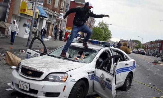 Manifestante salta sobre um carro da polícia danificado durante confrontos em Baltimore. Vários policiais ficaram feridas nesta segunda-feira em confrontos violentos com os jovens, após o funeral de Freddie Gray, que morreu sob custódia da polícia Foto: SHANNON STAPLETON / REUTERS