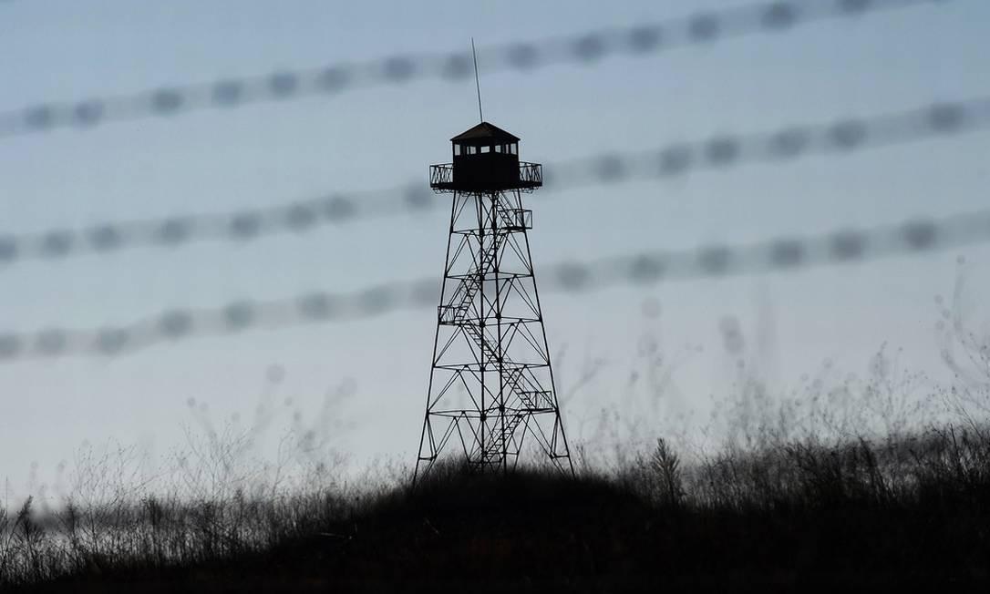 Uma torre de vigilância pode ser vista junto a cercas de arame farpado em território búlgaro, na fronteira com a Turquia Foto: AFP / Dimitar Dilkoff