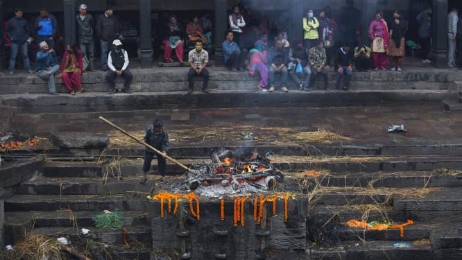 Nepaleses assistem a cremação de uma vítima do terremoto de sábado no templo de Pashupatinath, nas margens do rio Bagmati, em Katmandu Foto: Bernat Armangue / AP