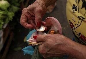 Mulher conta dinheiro em mercado do Rio de Janeiro Foto: Dado Galdieri / Bloomberg News