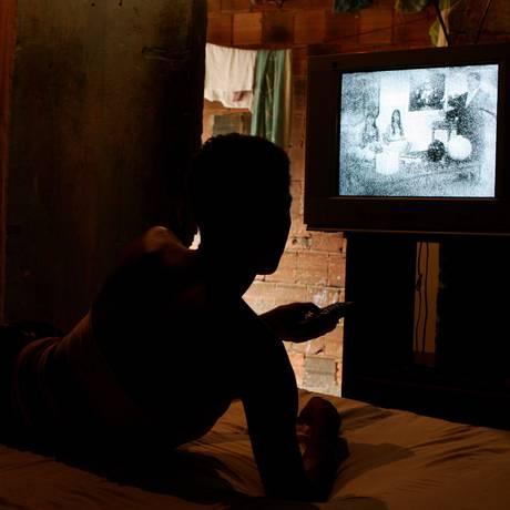 Homem assiste à TV em comunidade no Rio Foto: Gustavo Stephan / Agência O Globo