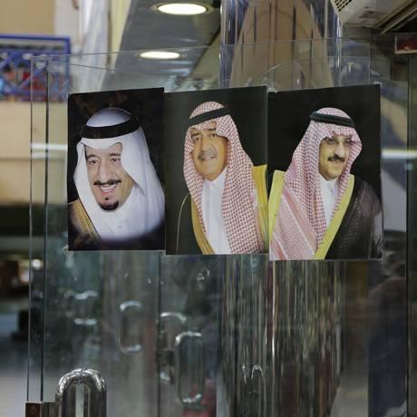 Fotos de Salman (e), Muqrin (c) e bin Nayef (d) em um mercado em Riad. Herdeiro da coroa foi destituído Foto: Hasan Jamali / AP