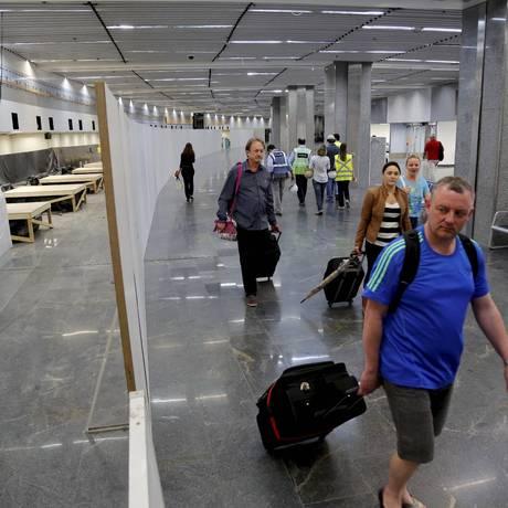 Improviso. Passageiros caminham ao lado de obras de reforma da Infraero interrompidas no Terminal 1, no Galeão Foto: Marcelo Piu / Agência O Globo
