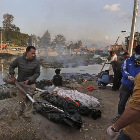 Shakar Pradhan carrega os corpos de familiares mortos no terremoto de sábado. Mais de 5 mil pessoas morreram no maior terremoto a atingir o Nepal desde 1934 Foto: Manish Swarup / AP