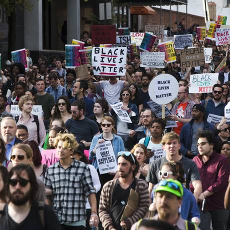 Manifestantes marcham por Baltimore com cartazes com os dizeres
