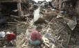 Em Bhaktapur, nepaleses são vistos em meio a escombros após terremoto