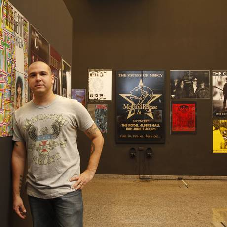 Alessandro Alr em meio aos poster da mostra 80/80, na exposição Maldita 3.0 Foto: Agência O Globo / Eduardo Naddar