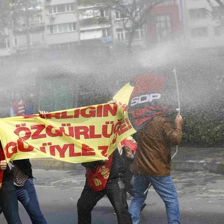 Manifestantes tentam se proteger durante um confronto com a polícia na Praça Taskim, em Istambul. Policias utilizaram jatos de água e bombas de gás para dispersar as pessoas Foto: MURAD SEZER / REUTERS