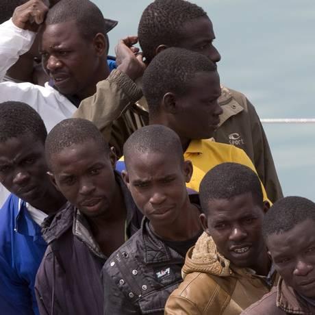 Sobreviventes. Migrantes fazem fila para desembarcar em Catânia de navio da guarda costeira italiana que os resgatou no Mar Mediterrâneo Foto: Alessandra Tarantino / AP/24-4-2015