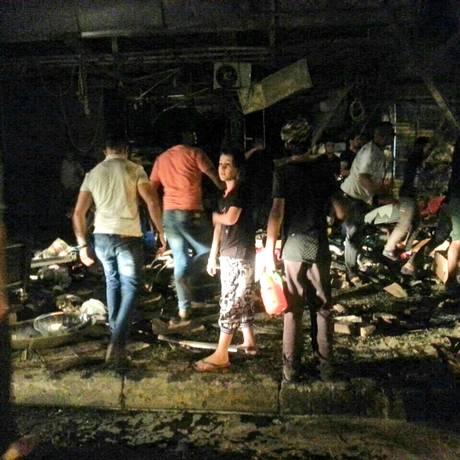 Civis inspecionam restos de carro-bomba que explodiu em Bagdá Foto: Hadi Mizban/AP