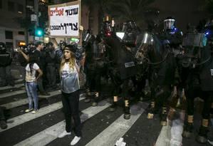 Manifestante segura cartaz em frente à linha de policiais montados em cavalos Foto: BAZ RATNER/REUTERS