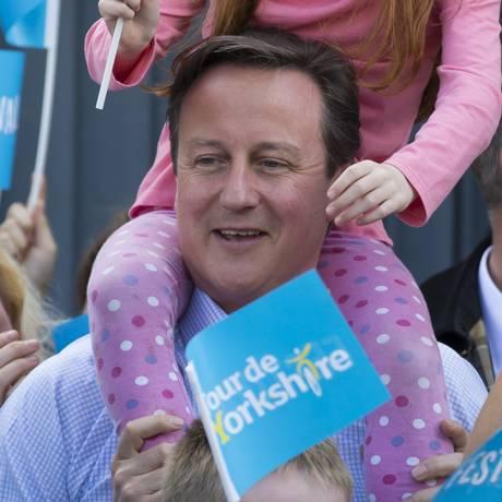 Futuro. Cameron põe criança nos ombros durante ato de campanha: premier acena com programa de moradias Foto: Jon Super/AP