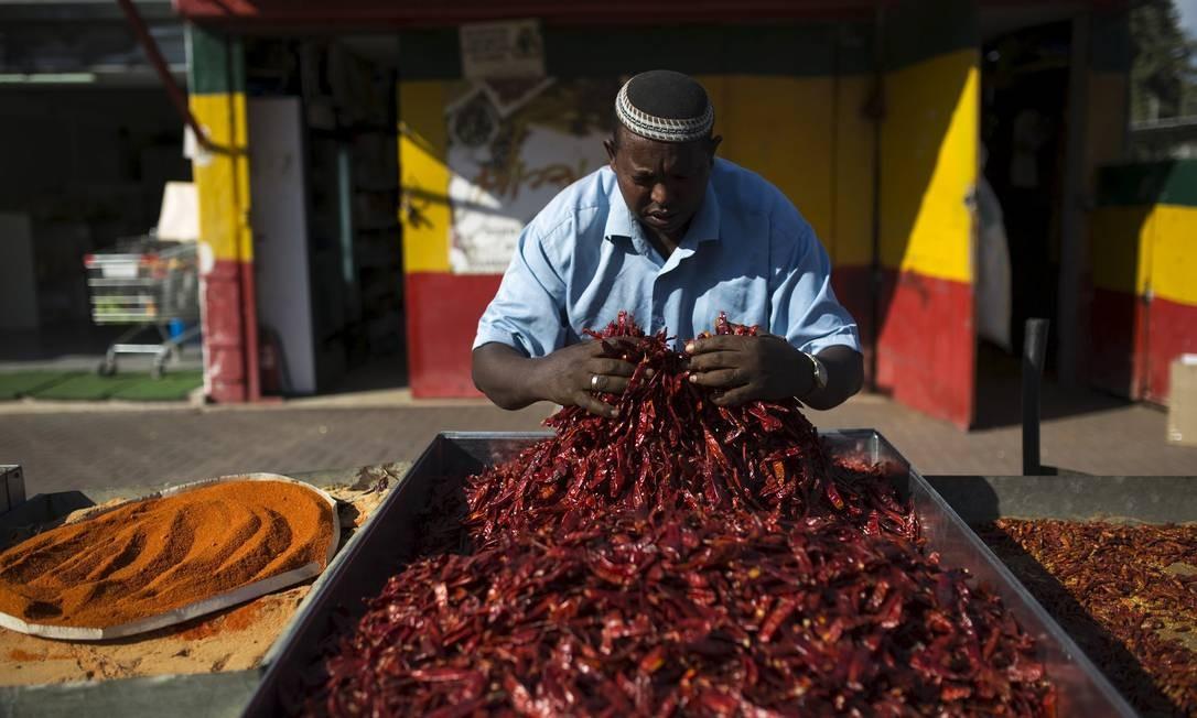 Um israelense de ascendência etíope mistura pimentas fora de sua loja de especiarias na cidade de Rehovot, perto de Tel Aviv Foto: AMIR COHEN / REUTERS