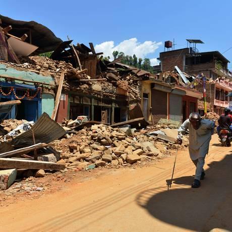Nepaleses caminham por rua em ruínas na cidade de Trishuli, no distrito de Nuwakot, norte de Katmandu. Foto: PRAKASH MATHEMA/ AFP