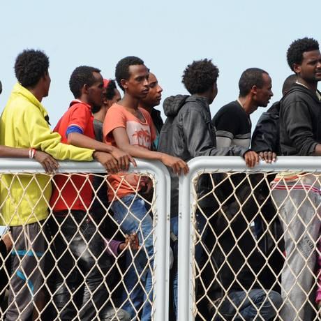 No porto de Salerno, sul da Itália, imigrantes aguardam para desembarcar após uma operação de resgate Foto: MARIO LAPORTA / AFP