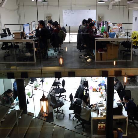 Trabalhadores em escritório Foto: Tomohiro Ohsumi / Bloomberg News