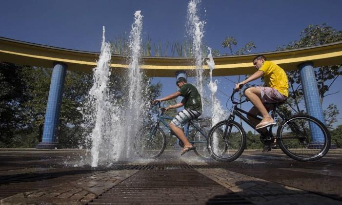 Jovens andam de bicicleta em meio a fontes à beira do Paraíba do Sul Foto: Antonio Scorza / Agência O Globo