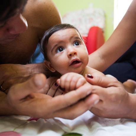 A bebê Larissa entre os pais, Rogério e Ariane Foto: Bárbara Lopes / Agência O Globo