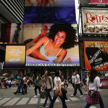 Pedestres passam em frente aos painéis luminosos de Times Square Foto: SPENCER PLATT / AFP